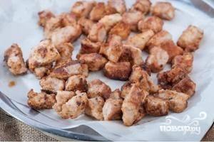 Перекладываем поджаренное мясо на салфетки, чтобы жир и масло впиталось. Затем солим его и перчим.