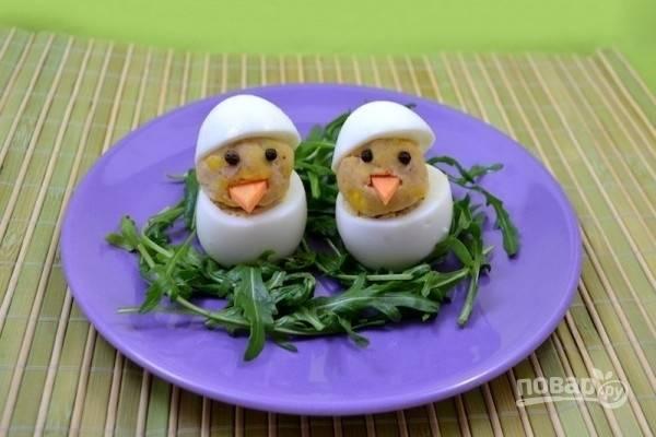 7.Для глазок используйте горошины черного перца, для клювиков – маленькие треугольнички из свежей моркови. Поставьте фаршированные яйца в холодильник до подачи на стол. Приятного аппетита!