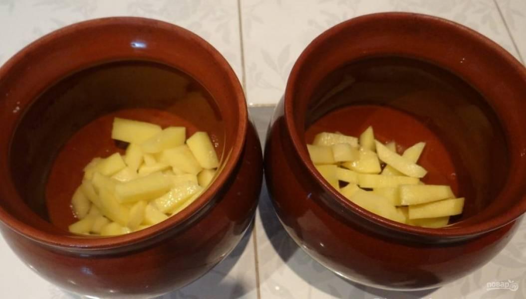 Возьмите горшочки. В каждый налейте по ложке масла. Поровну распределите картофель.