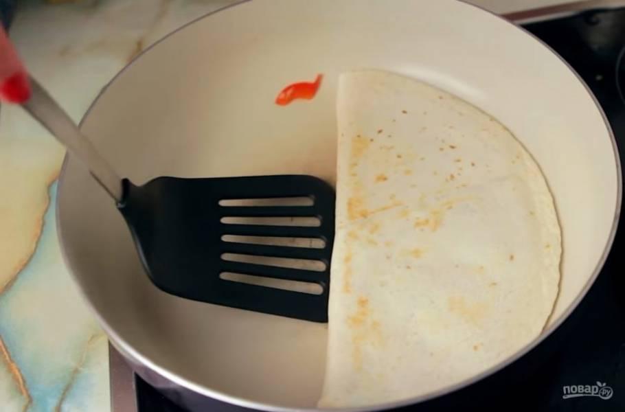 4.  Аккуратно заверните вторую половину тортильи и обжарьте с обеих сторон до хрустящей корочки. Разрежьте на порции. Приятного аппетита!