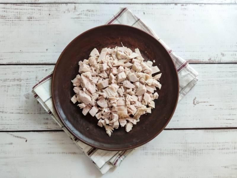 Остывшую курицу нарежьте маленькими кусочками и выложите на дно тарелки.