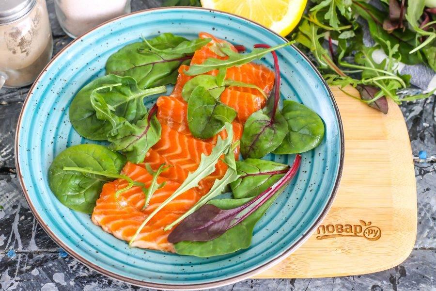 После чего промойте свежую зелень, нарвите ее руками на тарелку и выложите на нее ломтики промаринованной рыбы. Сверху дополните блюдо зеленью.