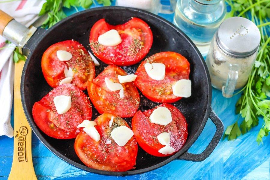 Очистите чесночные зубчики от шелухи, промойте в воде и нарежьте слайсами. Добавьте к томатам и потушите все на умеренном нагреве примерно 15 минут.