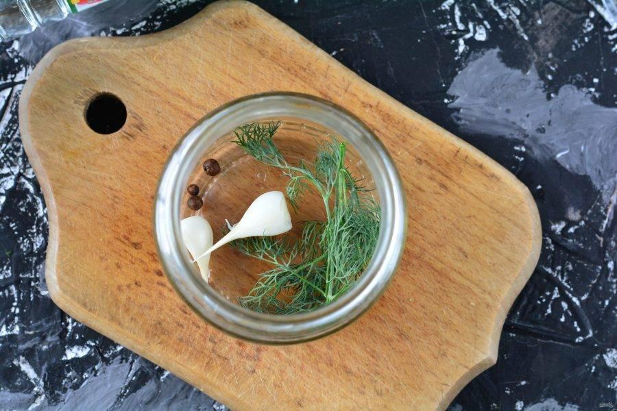 На дно чистых банок выложите чеснок, немного укропа и перца горошком.