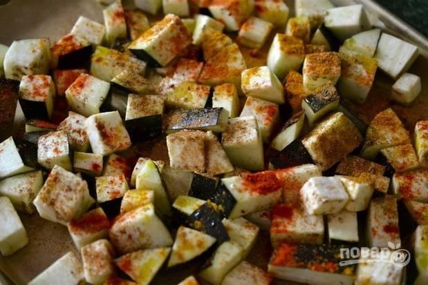 2.Противень застелите пергаментом и выложите баклажаны, распределите их в один слой. Полейте баклажаны оливковым маслом и добавьте все специи.