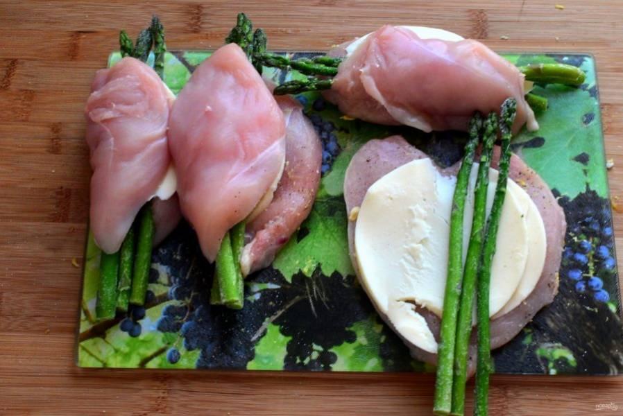 Вложите внутрь каждого филе по ломтику сыра и по три стебля спаржи. Закройте филе.