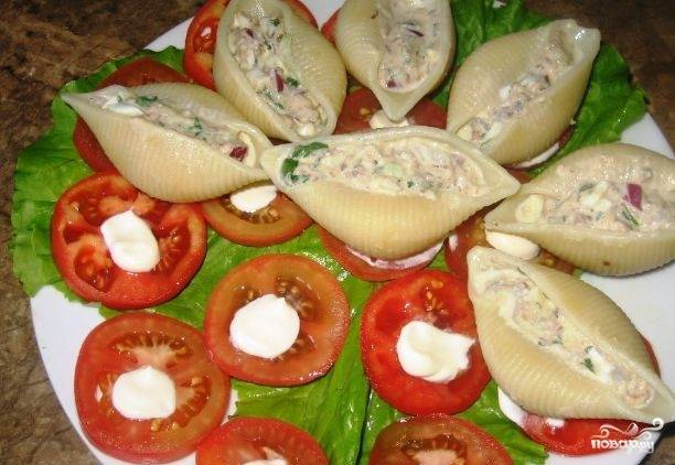 """На тарелку для подачи выложите промытый салат. Помидор помойте и нарежьте кружками. Выложите их на салат, украсив майонезом. """"Ракушки"""" начините салатом."""