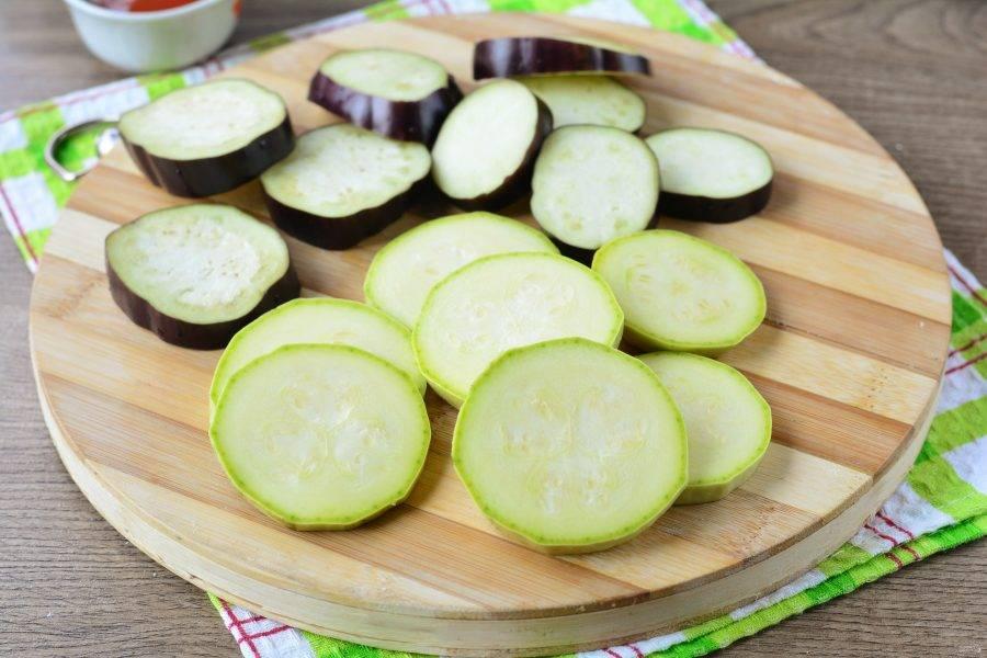 Промойте баклажаны и кабачки, срежьте хвостики, нарежьте овощи средними кружочками.