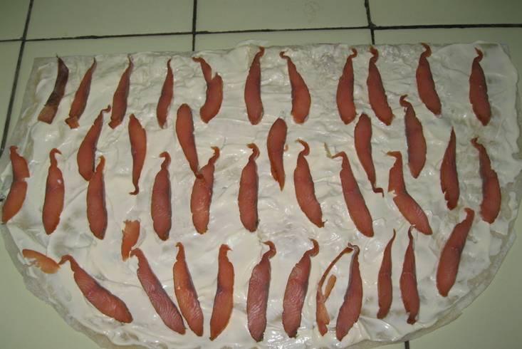 Сверху выкладываем тонко нарезанную красную рыбу.