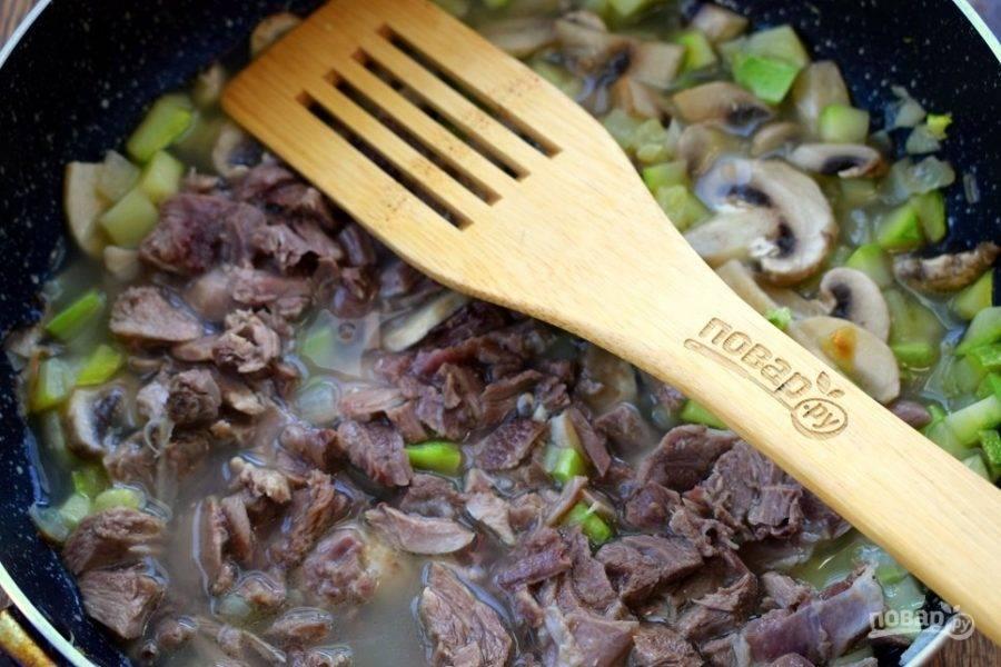Добавьте кусочки куриного мяса, влейте бульон так, чтобы он покрыл мясо. Тушите на медленном огне в течение 15 минут.