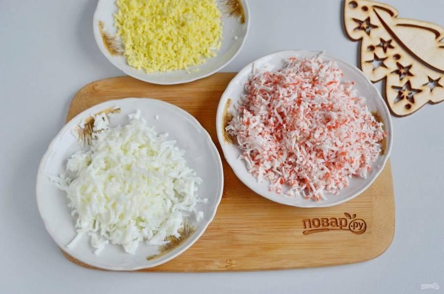 Отварите яйцо, разделите его на белок и желток и натрите на мелкой терке в разные тарелочки. Крабовые палочки лучше заморозить, а потом потереть.