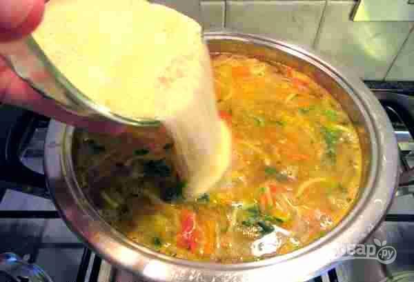 Суп посолите и постепенно всыпьте манную крупу, перемешивая суп, чтобы не образовались комочки.