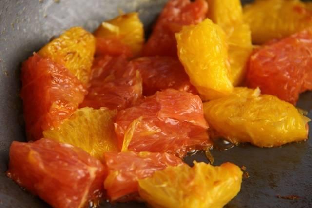 Очистите и порежьте кубиками цитрусовые, обжарьте их на сковороде с небольшим добавление масла. Обжаривайте примерно 5-7 минут.