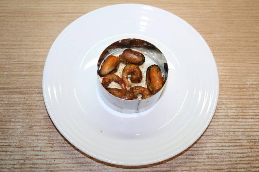 На слой риса выложите мидии и креветки.