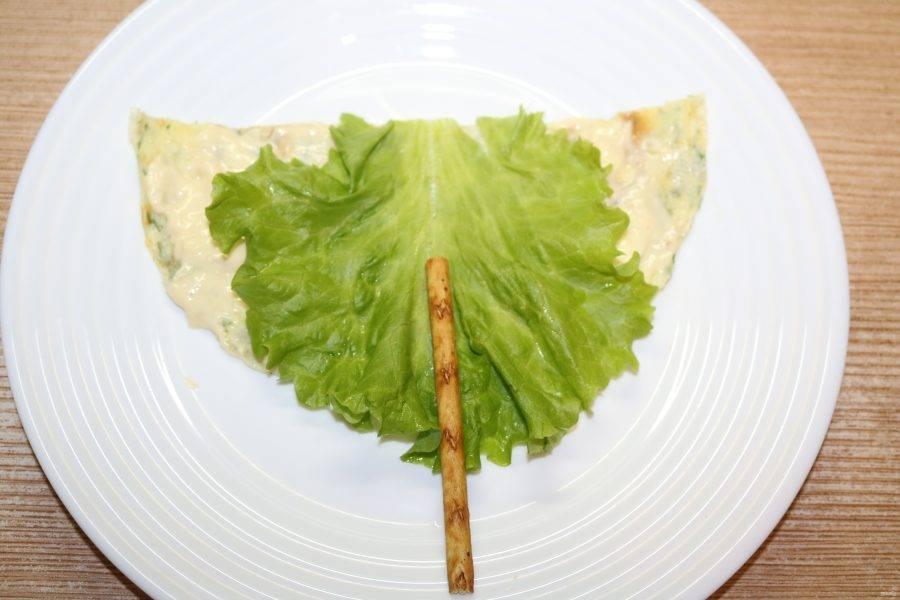 Положите сверху листик салата и палочку.