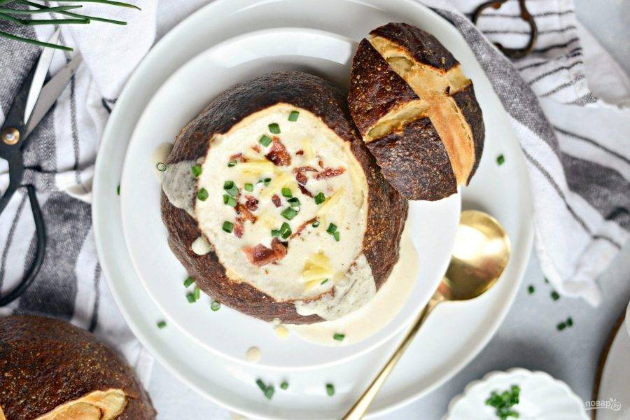 7. Подавайте пивной суп в хлебе, освободив буханку от мякиша. Сверху добавьте кусочки зелёного лука и бекона. Приятного аппетита!