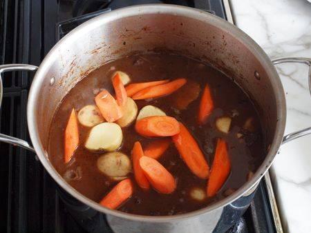 Добавьте крупно нарезанные морковь и картофель. Тушите до готовности овощей.