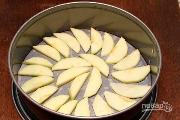 1. Яблоки вымойте, очистите и нарежьте тонкими пластинками. Форму застелите пергаментом и смажьте сливочным маслом. Выкладывайте яблоки в форму.