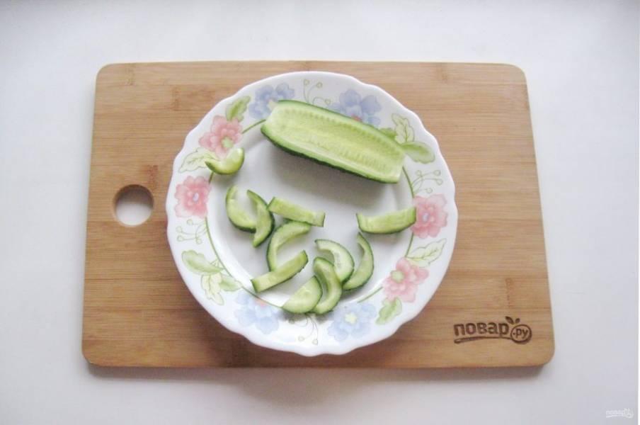 Огурец помойте, разрежьте на две части вдоль, удалите семена и нарежьте небольшими кусочками.