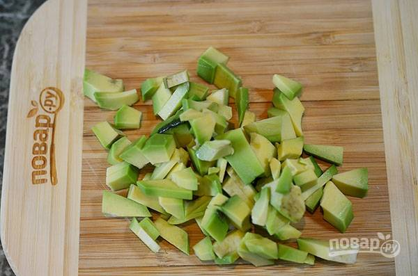 Для начинки: авокадо нарежьте кубиком. В чаше блендера измельчите вместе со сметаной.