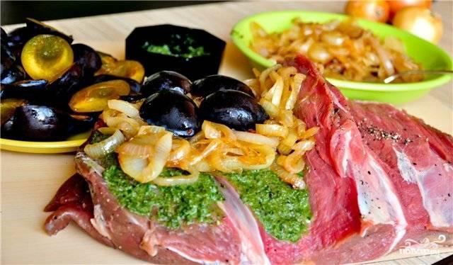 Мясо посолите, поперчите. Сначала смажьте обильно зеленью с чесноком, потом выложите лук и (сверху) сливы.