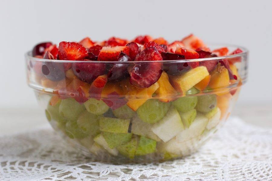 Фрукты и ягоды очистите от косточек и произвольно нарежьте на кусочки. Виноград и другие мелкие ягоды можно оставить целыми.