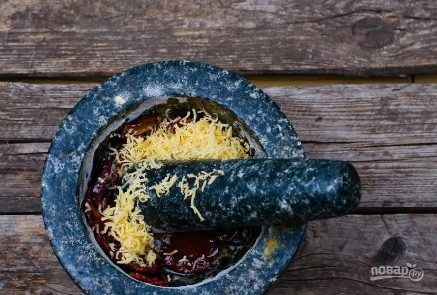 Переложите в ступку вяленые помидоры, добавьте к ним немного масла из банки. Натрите на мелкой терке сыр и добавьте его к помидорам. Тщательно потолките ингредиенты пестиком.