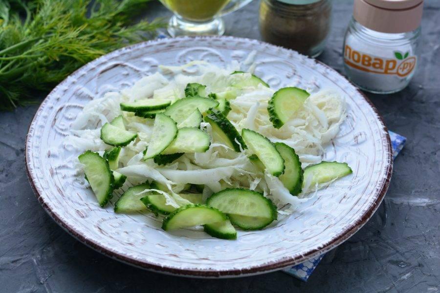 Выложите на блюдо огурцы и пекинскую капусту.