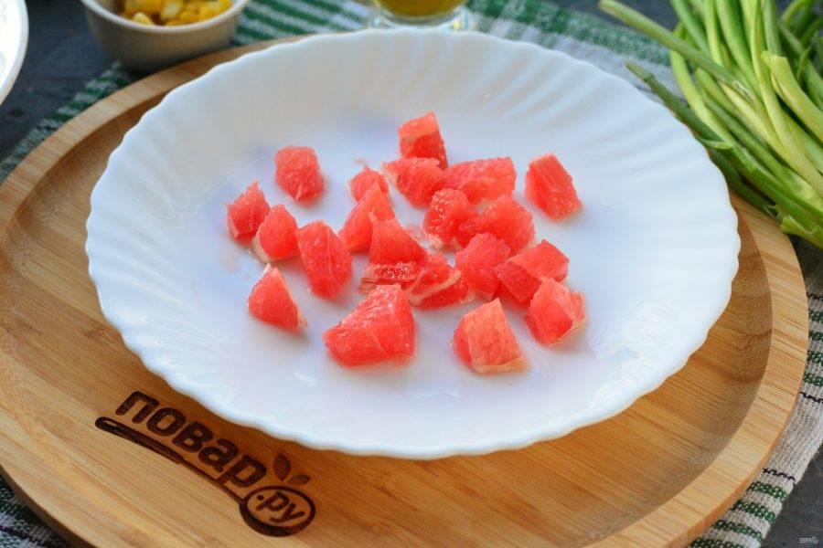 Срежьте кожуру с грейпфрута, нарежьте мякоть кубиками небольшого размера.