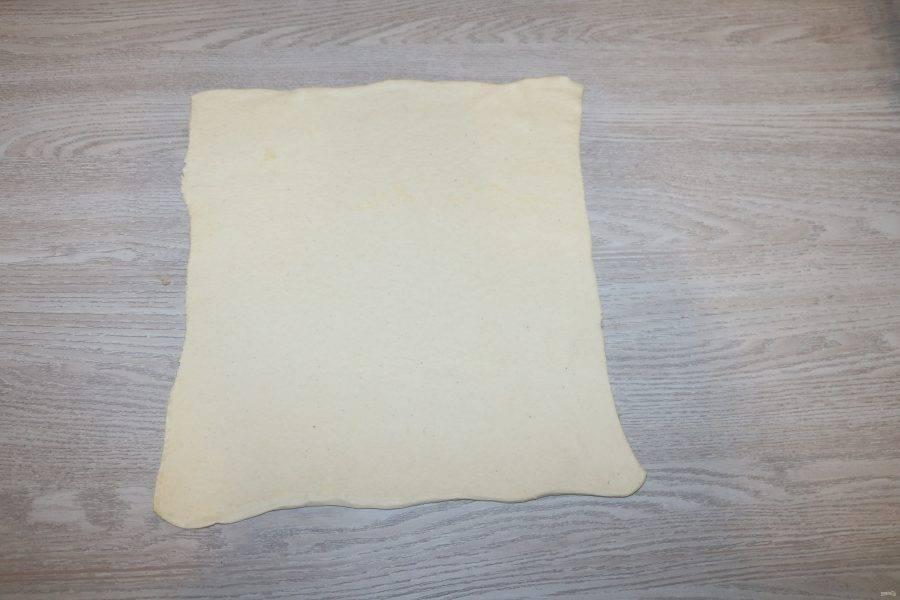 Размороженное тесто немного раскатайте в одном направлении в пласт толщиной 3 мм.
