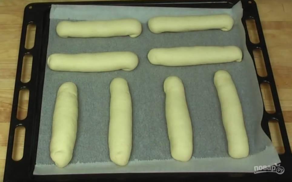 Придайте форму булочек, сверху их нужно помазать яичным желтком.