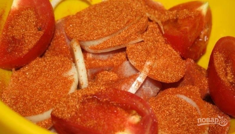 К свинине добавьте лук, нарезанный кольцами, и помидор, нарезанный дольками. Засыпьте продукты приправой.