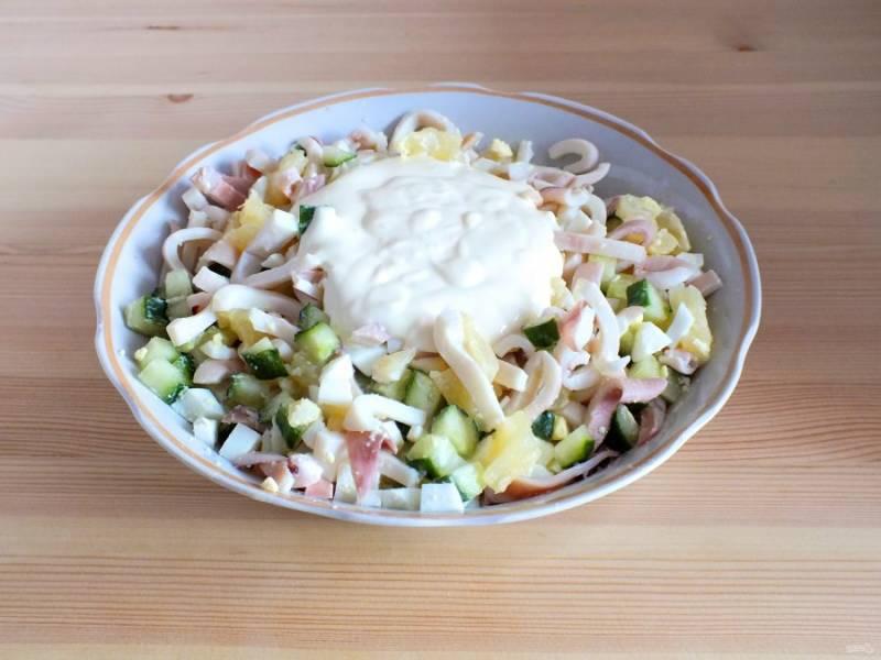 В салатник добавьте нарезанные кальмары, заправку.