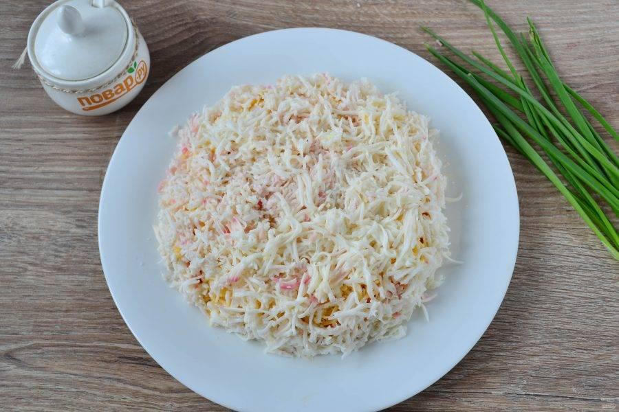 Вареные яйца разделите на белки и желтки. Белки натрите на мелкой терке и выложите на сыр. Смажьте майонезом.