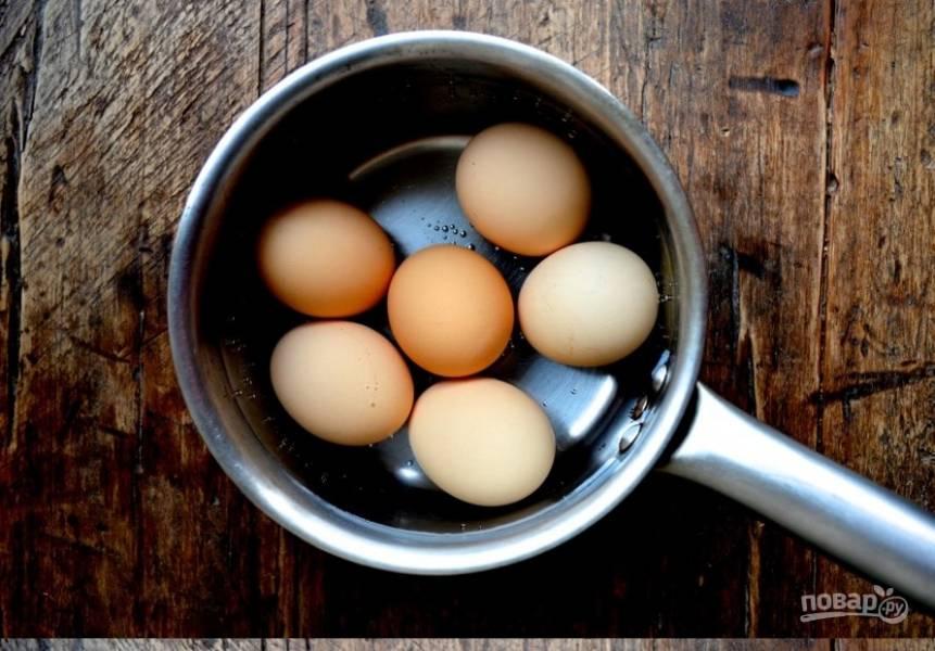Отварите яйца: сначала поставьте на огонь в кастрюльке с холодной водой, дайте закипеть, выключите огонь и дайте постоять в горячей воде 5 минут. Потом обдайте холодной водой и переложите яйца в тарелку.