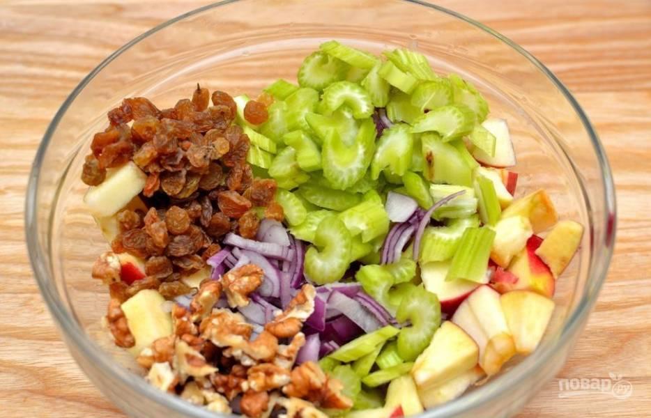 В салатницу добавьте нарубленный орех, нарезанный сельдерей и лук, а также изюм.