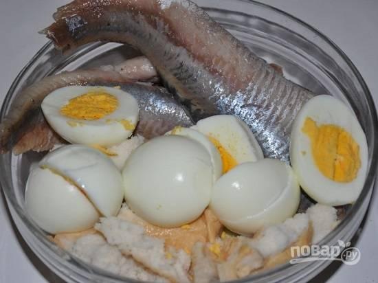 Очистим вареные яйца и отжимаем размоченные кусочки хлеба.