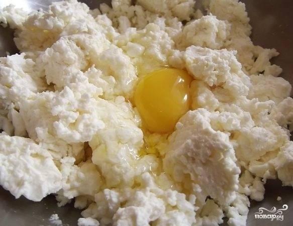 6. Разогрейте духовку, выложите тесто на дно жаропрочной формы, смазанной маслом. Теперь можно приступать к начинке. Выложите творог в глубокую мисочку, вбейте яйца.