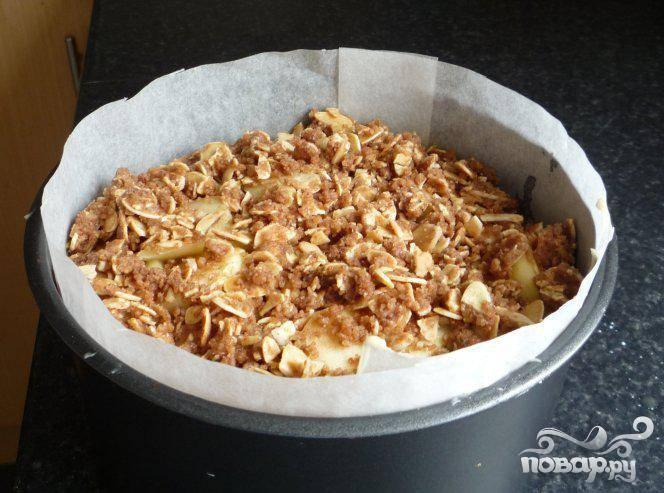 4.Ложкой выложите приблизительно 2/3 смеси для пирога в форму для выпечки, посыпать 1/3 посыпки сверху. Добавить оставшуюся смесь для пирога, выложить яблоки и остатки посыпки сверху. Запекать 1 час 15 минут или до готовности. Готовность проверить зубочисткой. Дать немного остыть, перед тем, как достать из формы. Подавать горячим или холодным.