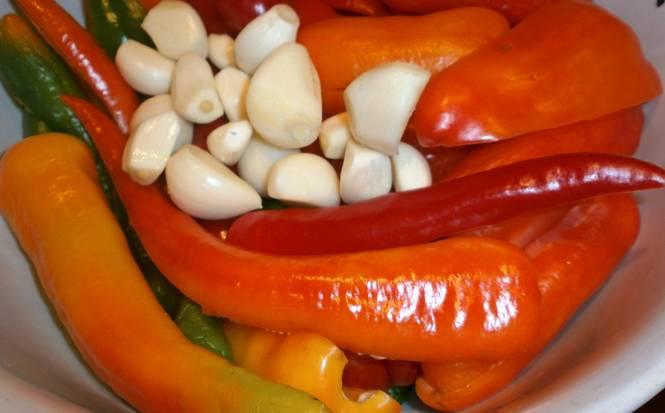 Чеснок и хрен очищаем, мелко нарезаем. У перцев удаляем плодоножки и семена. Складываем все овощи в блендер и измельчаем до однородной массы.