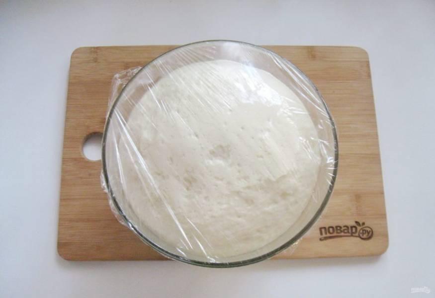 Миску с тестом накройте пищевой пленкой, поставьте в теплое место и дайте подойти.