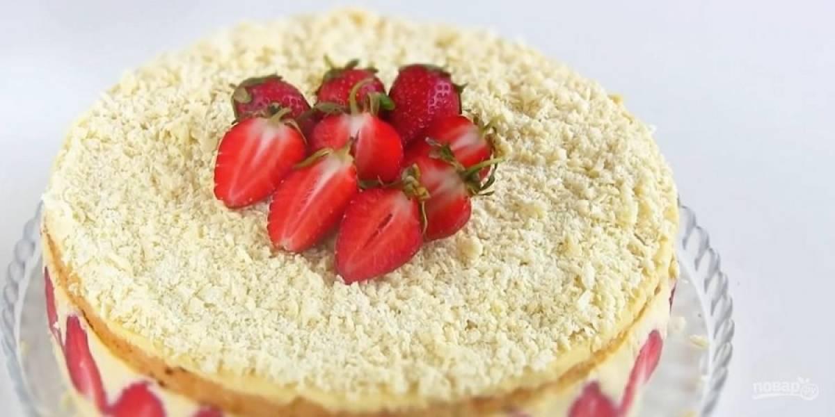 10. Накройте торт пленкой и отправьте в холодильник на 8 часов. Снимите пленку, кольцо и украсьте торт тертым белым шоколадом и клубникой. Приятного аппетита!