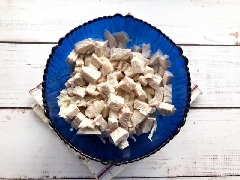 Индейку сварите, дайте ей полностью остыть, нарежьте небольшими кусочками и добавьте к капусте.