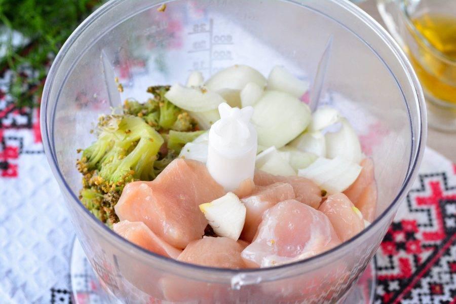 Промойте куриную грудку, почистите лук. Нарежьте средними кусочками мясо и лук. Сложите в чашу блендера. Туда же добавьте размороженные кусочки капусты брокколи.