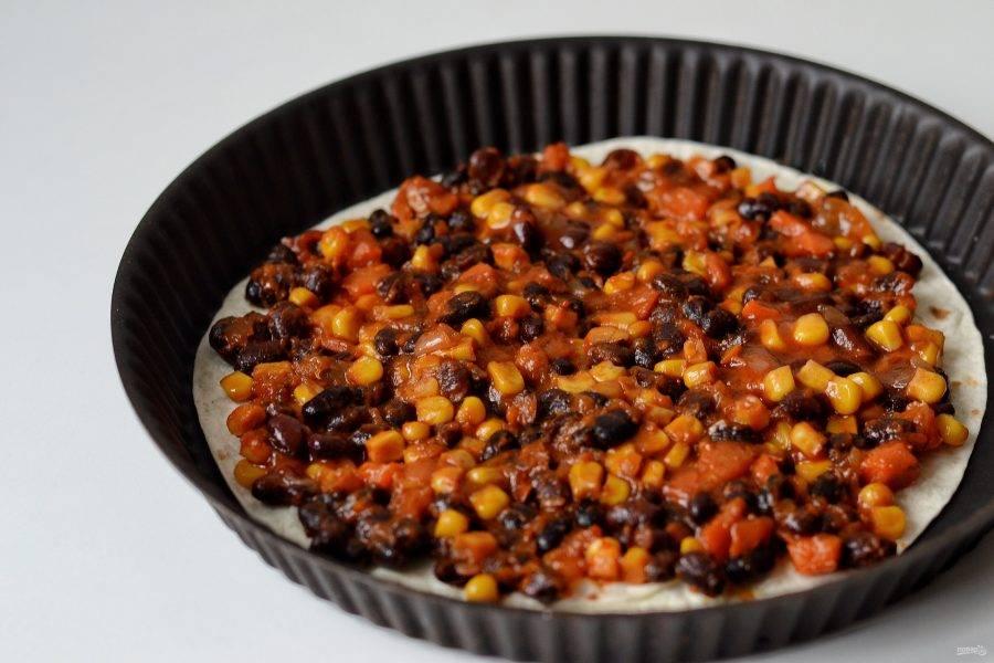 Переложите тортилью на противень или в формы для выпечки. Сверху толстым слоем выложите фасоль с кукурузой.