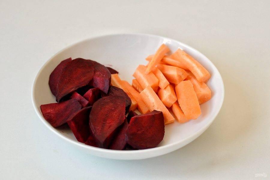 Очистите морковь и свеклу. Нарежьте свеклу дольками, а морковь брусочками примерно такого же размера.