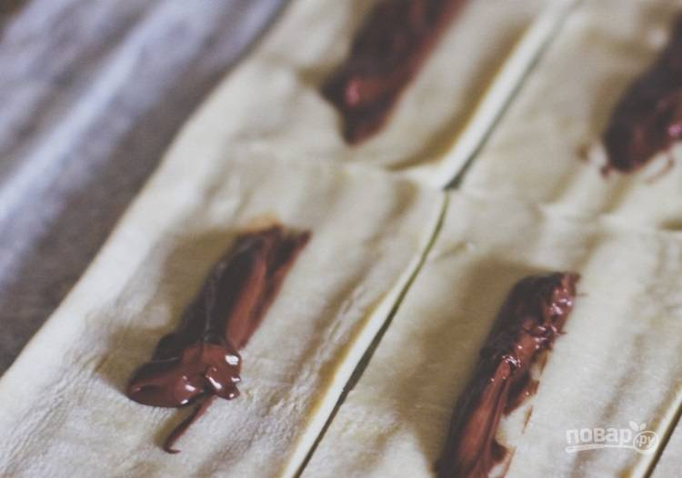 2.Выложите в центр каждого прямоугольника около 1 чайной ложки шоколадно-ореховой пасты, распределив ее вдоль.