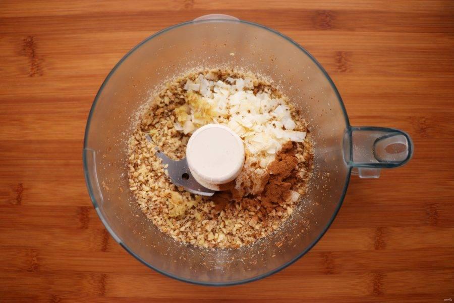 Затем добавьте к орехам кокос, корицу, натертый имбирь и зернышки кардамона.