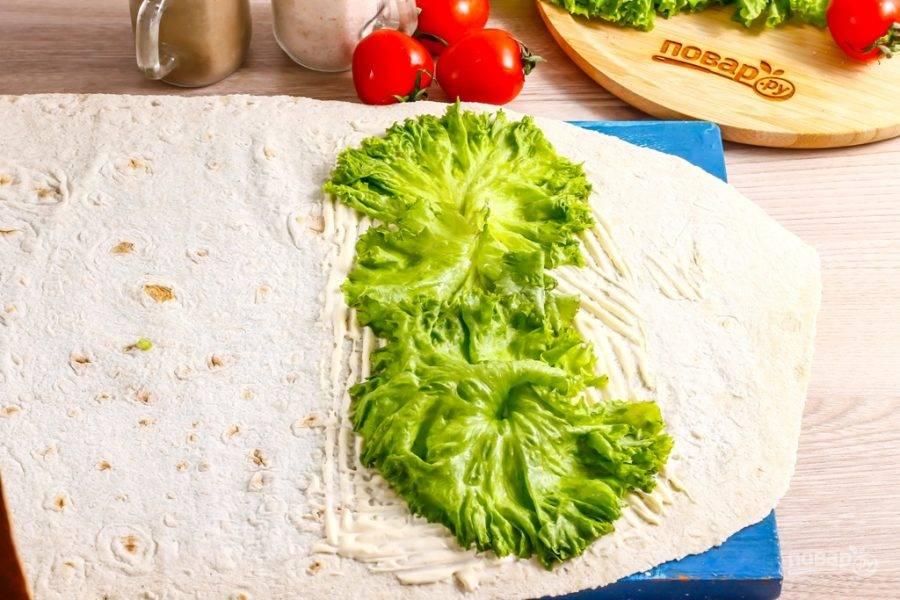 Разверните на рабочей поверхности лист лаваша, обмажьте его 1 ст.л. майонеза и выложите на соус промытые салатные листья.