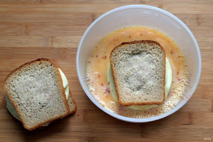 Венчиком хорошо взбейте яйца со смесью молока и сливок. Добавьте паприку, черный перец и чесночный порошок. Посолите по вкусу и еще раз перемешайте. Хорошенько обмакните будущие чизбургеры в молочно-яичную смесь, чтобы хлеб пропитался.